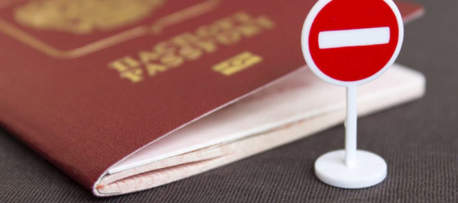 Stop illegal migration concept, Russian passport and stop sign close up